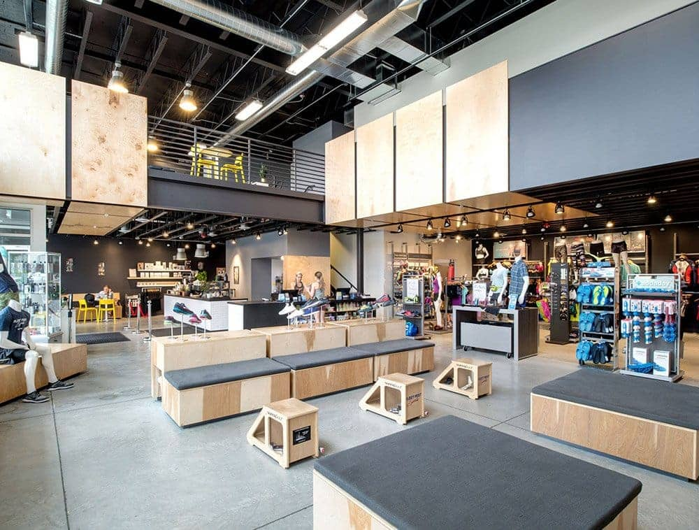 Stylish black open web trusses are displayed overhead in a retail setting