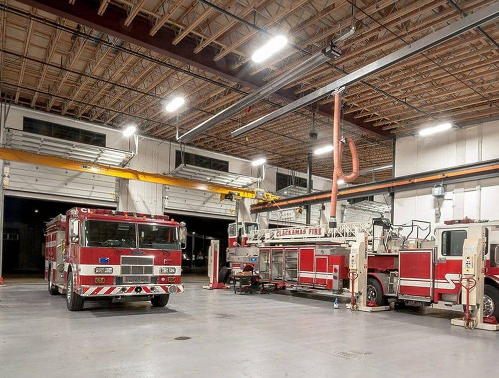 A fire station at night features open web trusses over its large trucks