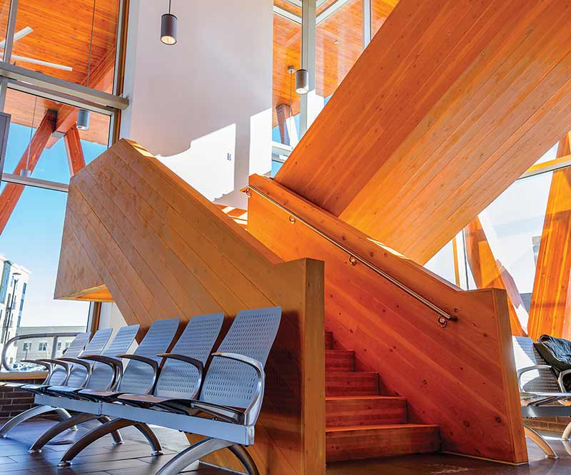 Solid wood staircase in front of full height windows in G.K. Butterfield Transportation Center