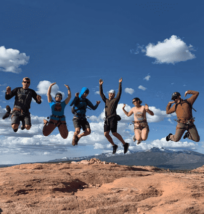 RedBuilt team members jump in front of a camera at an outing
