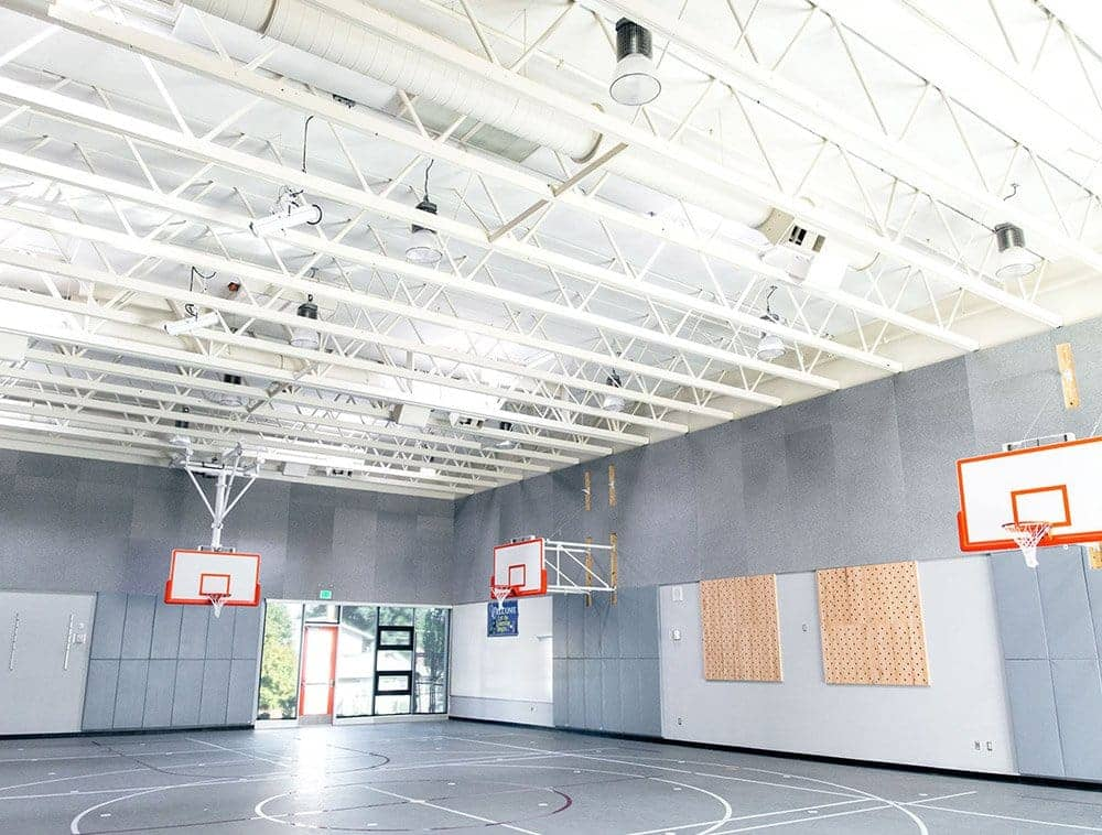 A basketball court featuring white trusses overhead
