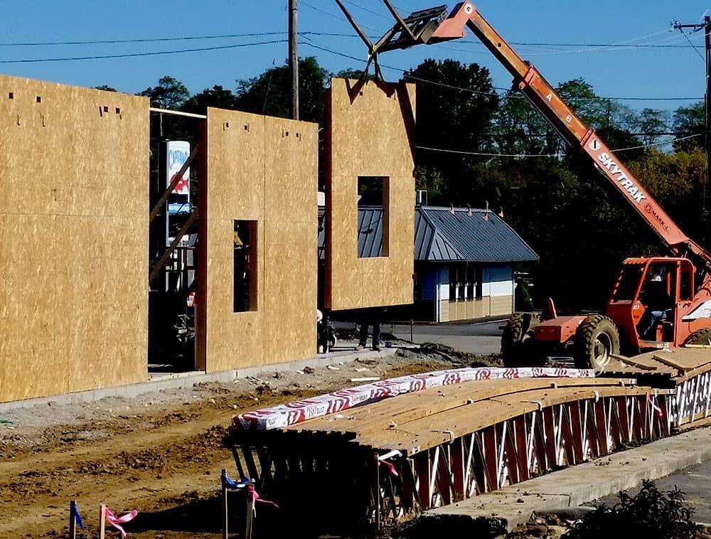 a crane lifts a wall panel